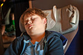 Child is sleeping in the aircraft in his seat — Stock Photo