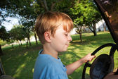 Boy likes to drive an electric car in an old palace of a former — Stock Photo