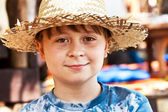 Young boy with straw hat is happy and smiles — Stock Photo