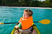 Boy paddles in a canoe at the ocean with safety west — Stock Photo