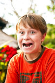 Young boy sitting in a beach restaurant makes funny faces — Stock Photo