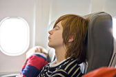 Boy sleeping in the aircraft — Stock Photo