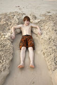 Boy is lying in a sandy bed at the beauti ful beach — Stock Photo