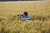 Chłopiec robienia zdjęć ze statywu liści w polu kukurydzy — Zdjęcie stockowe
