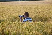 Menino tirando fotos com o tripé das folhas no campo de milho — Foto Stock