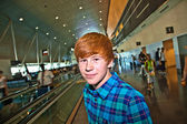 Young boy on a moving staircase inside the airport — Stock Photo