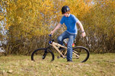 Young boy is riding with the dirtbike and racing in the landscap — Stock Photo