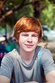 Boy with red hair and pickax in the face looks happy — Stock Photo