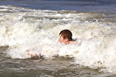 Young boy is body surfing in the waves of the ocean — Stock Photo