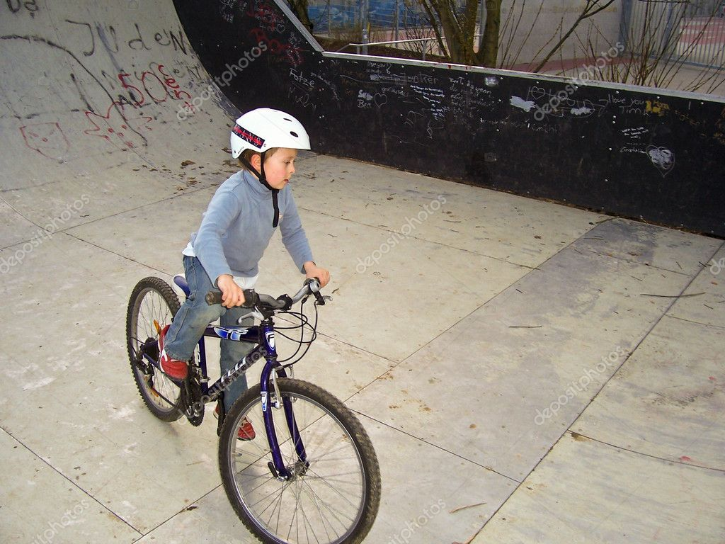 Joung boy with his mountainbike trains BMX tricks in the ...