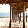 Beach with old wooden pier — Stock Photo