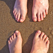 Feet of father and son at the wet sand of the beach — Stock Photo #5684009