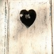 Old wooden door with a carved romantic heart — Stockfoto