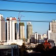 Electrical cable in front of skyscrapers and small houses in Ban — Stock Photo
