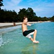 Boy is enjoying the clear warm water at the beautiful beach but — Stock Photo