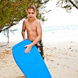 Stock Photo: Young boy at the beach with surf board is smiling and looking se