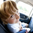 Boy sitting in fond of a car having fun — Stock Photo