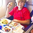 Boy enjoys the dinner in the aircraft — Stock Photo #5688578