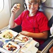 Boy enjoys the dinner in the aircraft — Stock Photo #5688607