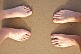 Feet of a couple at the beach — Stock Photo