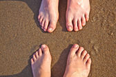 Feet of father and son at the wet sand of the beach — Stockfoto