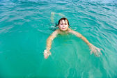 Young boy is swimming in the warm clear sea and enjoying the vac — Stock Photo