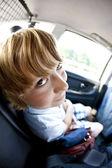 Boy sitting in fond of a car having fun — Stock Photo