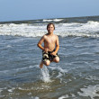 Jumping boy enjoys the beautiful ocean with waves — Stock Photo #5690233