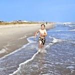 Boy runs along the beautiful beach — Stock Photo #5690280