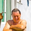 Man has a shower in the garden — Stock Photo