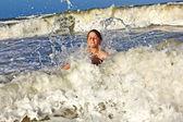 Dziecko ma zabawy w fale oceanu — Zdjęcie stockowe