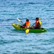 Father and son are padelling with a canoe on open sea — Stock Photo