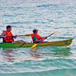 Father and son are padelling with a canoe on open sea — 图库照片