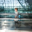Boy in the departure hall  in the new Airport on a moving stairc — Stockfoto