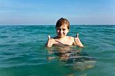 Chico con el pelo rojo está disfrutando el agua clara caliente en el beauti — Foto de Stock