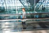 Menino no salão de partida no aeroporto de novo em um stairc em movimento — Fotografia Stock