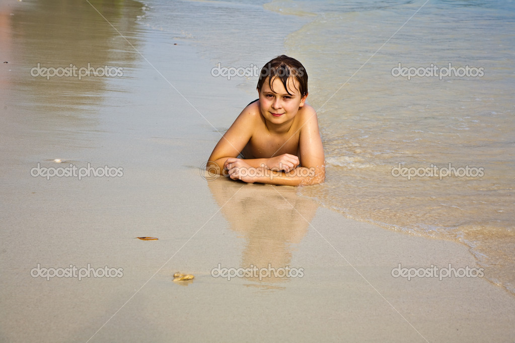 Young boy is lying at the beach and enjoying the warmness of the water and looking self confident and happy — Stock Photo #5715494