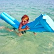 Boy enjoys the air matress in the sea - Stock Photo