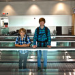 Young boys on a moving staircase inside the airport — Foto de Stock