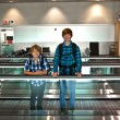 Young boys on a moving staircase inside the airport — Foto Stock