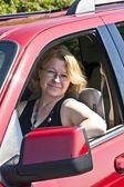 Gülümseyen kadın kırmızı bir araba kullanıyor — Stok fotoğraf