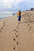 Woman walking along the beach — Стоковое фото