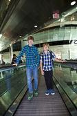 Unga pojkar på en moving trappa inne på flygplatsen — Stockfoto