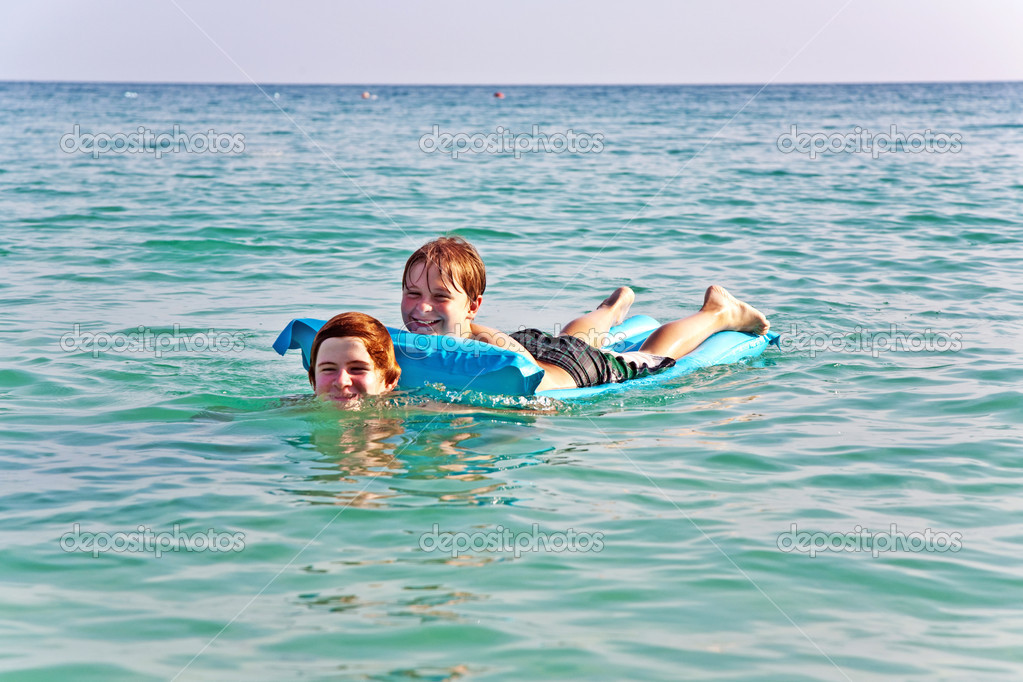 Brothers are playing together in a beautiful sea with crystal clear water and blue sky — Stock Photo #5723542