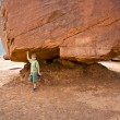 Постер, плакат: Monument Valley child has fun by simulatings to carry a big rock