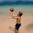 Boy is playing with a coconut on a beautiful beach — Stock Photo