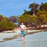 chico joven con el pelo rojo en traje de baño está ejecutando a lo largo de la playa — Foto de Stock