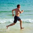 Man is running along the beautiful beach — Stock Photo #5779138