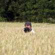Fotographer in corn field with camera — Stock Photo #5779547