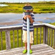 Boy watching the nature through a binocular — Stock Photo